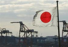 Японский флаг на фоне контейнерного терминала в порту Токио 19 декабря 2012 года. Япония зафиксировала рекордный дефицит торгового баланса в 2012 году, поскольку экспорт продолжил снижаться в декабре, сигнализируя, что усилия премьер-министра Синдзо Абэ по ослаблению иены набирают обороты медленными темпами. REUTERS/Yuriko Nakao