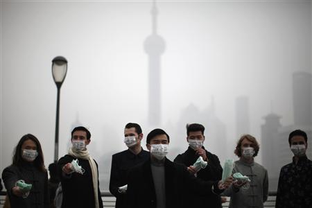 A group of expatriates stand along the Bund as they distribute face masks to pedestrians to raise awareness of air pollution in downtown Shanghai January 24, 2013. According with the U.S. consulate air quality readings, which measure PM2.5 particulates Shanghai's air quality was ''very unhealthy'' on Thursday. REUTERS/Carlos Barria