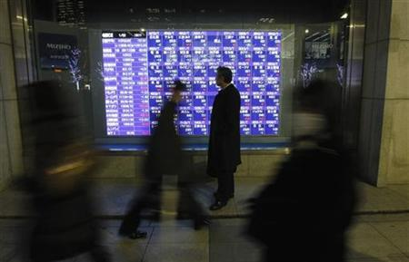 A man looks at a stock index board in Tokyo January 22, 2013. REUTERS/Kim Kyung-Hoon/Files