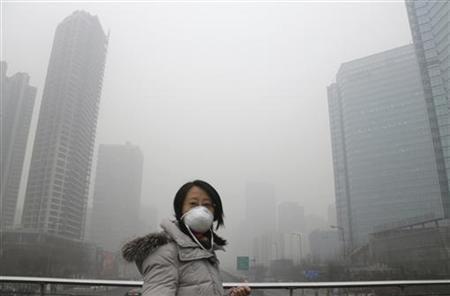 A woman wearing a mask walks on a pedestrian bridge on a hazy day in Beijing January 23, 2013. REUTERS/Jason Lee