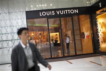 A man walks by a Louis Vuitton luxury boutique at the IFC Mall in Shanghai June 4, 2012. REUTERS/Carlos Barria (CHINA - Tags: BUSINESS)