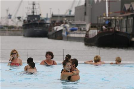 A couple enjoys a floating open-air swimming pool called a ''badboot'' in the port of Antwerp August 20, 2012. REUTERS/Francois Lenoir