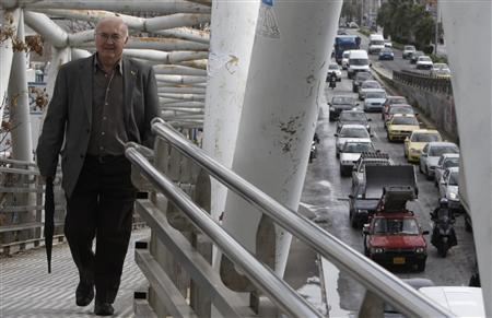 A man walks on a pedestrian bridge as vehicles stuck in a traffic jam at a main avenue during a 24-hour strike of workers at the Metro in Athens January 24, 2013. REUTERS/John Kolesidis