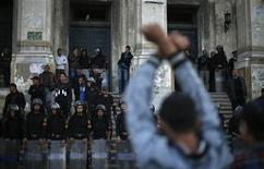 A protester gestures in front of a courthouse during a demonstration in Alexandria January 21, 2013. REUTERS/Suhaib Salem