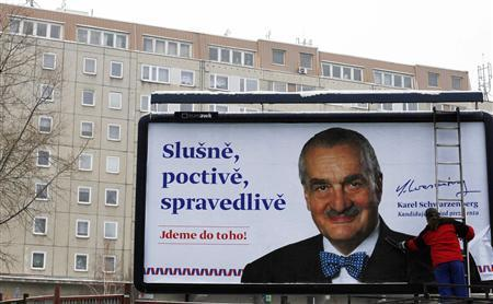 A worker adjust a billboard featuring the Czech presidential candidate Karel Schwarzenberg in central Prague January 22, 2013. REUTERS/Petr Josek