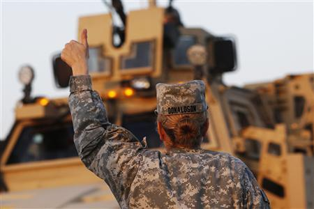 U.S. Army convoys are given a thumb up from a female soldier after crossing into Kuwait during the last convoy out of Iraq in this December 18, 2011 file photograph. REUTERS/Shannon Stapleton/Files