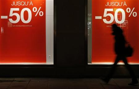 A man makes his way past a store window decorated with discount signs in Paris, January 9, 2013, during the start of winter sales in France. REUTERS/Christian Hartmann (FRANCE - Tags: BUSINESS SOCIETY)