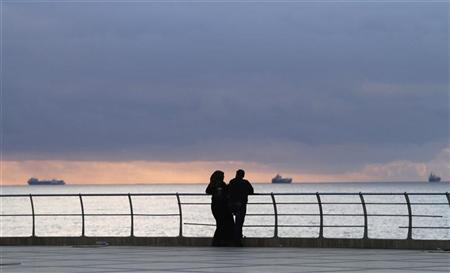 A man and a woman look out to the sea in Benghazi January 13, 2013. REUTERS/Esam Al-Fetori