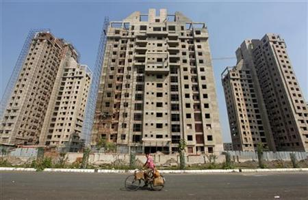 A man cycles past residential buildings under construction in Kolkata December 31, 2012. REUTERS/Rupak De Chowdhuri/Files