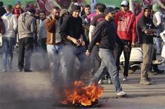 Egipto llega al segundo aniversario de la revuelta que derrocó a Hosni Mubarak con poco para celebrar: profundamente dividida y enfrentando una dura crisis económica, la nación se prepara para más protestas, pero esta vez contra un líder elegido en democracia. En la imagen, ultras de fútbol alrededor de neumáticos que han quemado sobre un puente durante una protesta pidiendo justicia para las 74 personsa que murieron en una estampida en un estadio el año pasado, en el centro de El Cairo, el 23 de enero de 2013. REUTERS/