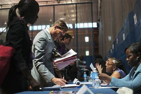 Job seekers speak to recruiters at a job fair sponsored by the New York Department of Labor in New York, June 7, 2012. REUTERS/Keith Bedford/Files