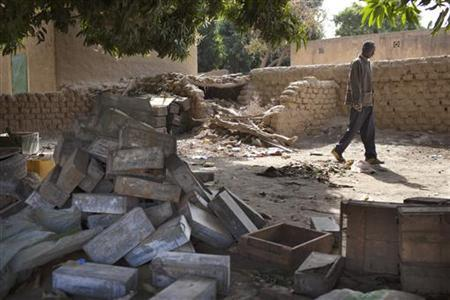 Local resident Issa Dembele stands next to munitions stockpiled in the courtyard of house in Diabaly January 23, 2013. REUTERS/Joe Penney (MALI - Tags: MILITARY CIVIL UNREST POLITICS CONFLICT)