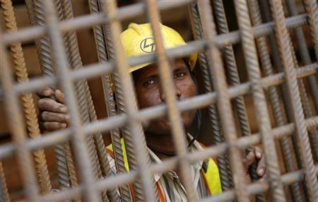 A Delhi Metro Rail Corporation employee looks through iron rods at the final tunnelling breakthrough of Qutub Minar and Saket stations in New Delhi June 17, 2009. REUTERS/Adnan Abidi/Files