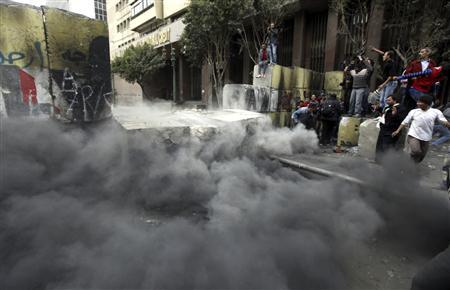 Protesters react as a dismantled concrete barrier falls at the Qasr al-Aini Street near Tahrir Square in Cairo January 24, 2013. REUTERS/Amr Abdallah Dalsh