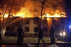 Полицейский спецназ у горящего здания в городе Исмаиллы, Азербайджан, где произошли массовые уличные беспорядки 24 января 2013 года. Полиция в четверг применила слезоточивый газ и водометы против сотен демонстрантов, которые окружили здание региональной администрации на северо-западе Азербайджана, а ночью сожгли несколько автомашин и отель. REUTERS/Aziz Karimov