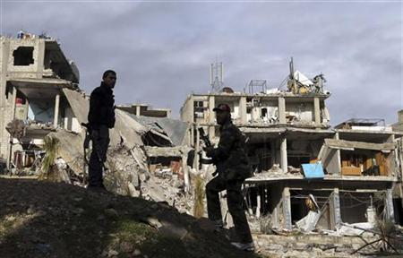 Free Syrian Army fighters stand in front of buildings destroyed by Syrian Army air strikes in the Arabeen neighbourhood of Damascus January 24, 2013. REUTERS/Goran Tomasevic