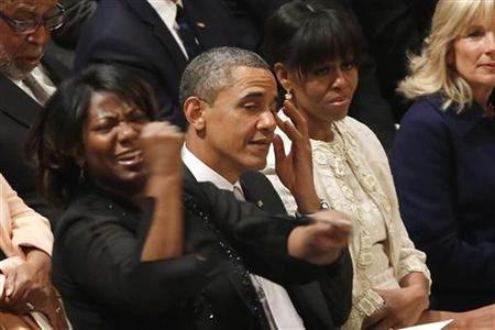 U.S. President Barack Obama (2nd L) wipes away tears as Michele Fowlin directs the Children of the Gospel Choir as they sing ''Determined to Go On'' during the Presidential Inaugural Prayer Service at the National Cathedral in Washington, January 22, 2013. REUTERS/Jonathan Ernst