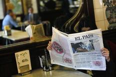"""El Gobierno venezolano rechazó enérgicamente el jueves la """"falsa foto"""" de un Hugo Chávez convaleciente que publicó El País, una imagen que fue retirada por el periódico español junto con una disculpa pública. En la imagen del 24 de enero, una mujer en un café de Madrid lee el ejemplar del diario con la foto falsa que fue retirado. REUTERS/Andrea Comas"""