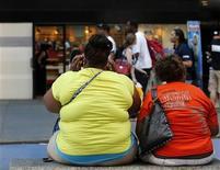 La obesidad, un factor clave en las enfermedades cardiovasculares y la diabetes, impone costes tanto al sector público como al privado y es un lastre para el crecimiento económico, pero los líderes empresariales reunidos en Davos no se ponen de acuerdo sobre qué pueden o deben hacer para afrontarla. En la imagen, dos mujeres obesas sentadas en un banco en Times Square, Nueva York, el 31 de mayo de 2012. REUTERS/Brendan McDermid