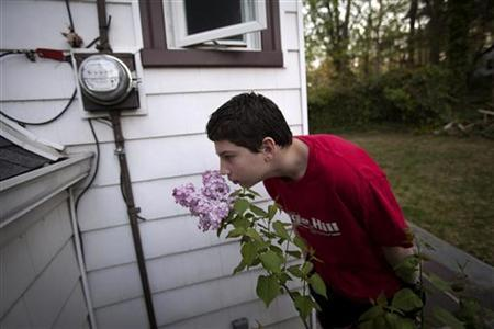 Matthew Kolen, who was diagnosed with Asperger's syndrome at age eight, smells a lilac that he had given his mother for her birthday, outside his home in Long Island, New York June 16, 2012. REUTERS/Shannon Stapleton