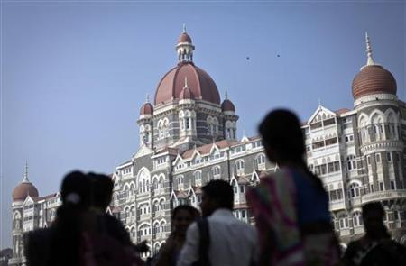 Tourists are silhouetted against the backdrop of the Taj Mahal hotel, which was one of the targets of the November 26, 2008 attacks, in Mumbai November 26, 2012. REUTERS/Danish Siddiqui/Files