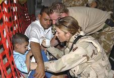 Foto de arquivo mostra a Sargento do Exército norte-americano, Michelle L. Thompson, ajudando uma criança em agosto de 2005, no Iraque. O Pentágono retirou nesta quinta-feira sua proibição a mulheres na linha de frente de combate, num passo histórico em direção à igualdade dos sexos nas Forças Armadas dos Estados Unidos, depois de 11 anos de guerra ininterrupta. 25/08/2005 REUTERS/Lek Mateo/DoD Photo/Handout