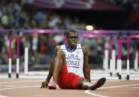 Cuba's Dayron Robles sits on the track after he suffered an injury during the men's 110m hurdles final during the London 2012 Olympics Games at the Olympic Stadium August 8, 2012. REUTERS/Lucy Nicholson