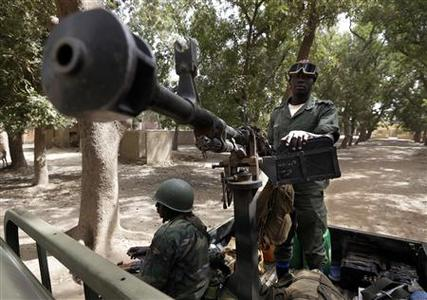 A Malian soldier stands guard near his machine gun in the town of Niono January 24, 2013. REUTERS/Eric Gaillard