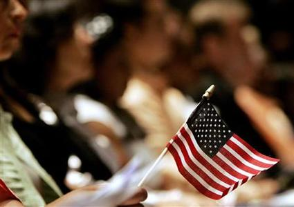 A woman holds an American flag during naturalization ceremonies for new citizens aboard the Intrepid in New York, July 6, 2006. REUTERS/Shannon Stapleton