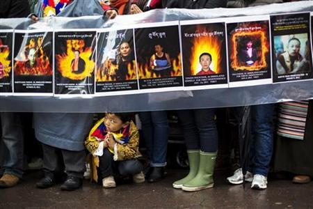 A child gestures at the feet of protesters holding a sign commemorating victims of self-immolation during a solidarity march from the Chinese Consulate to the United Nations (UN) Headquarters in support of Tibet in New York December 10, 2012. REUTERS/Lucas Jackson/Files