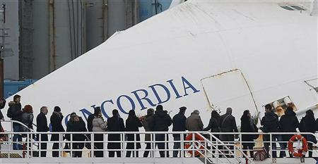 Relatives of victims stand on a ferry in front of the capsized cruise liner Costa Concordia outside Giglio harbour January 13, 2013. REUTERS/Tony Gentile (ITALY - Tags: DISASTER MARITIME ANNIVERSARY TPX IMAGES OF THE DAY)