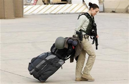 A member of U.S. security personnel pulls her luggage while waiting to depart from Iraq, at the former U.S. Sather Air Base near Baghdad December 15, 2011. REUTERS/Mohammed Ameen/Files
