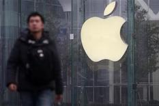 A man walks in front of a company logo outside an Apple store in downtown Shanghai January 24, 2013. REUTERS/Aly Song