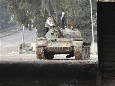 Young Syrian refugees play at a damaged tank near the border with Turkey at Bab El-Hawa on the outskirts of Idlib, January 20, 2013, in this picture provided by Shaam News Network. REUTERS/Redwan Al-Homsi/Shaam News Network/Handout