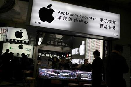Customers and sales persons are seen at an Apple maintenance service store at a mobile phone market in Shanghai, January 24, 2013. REUTERS/Aly Song