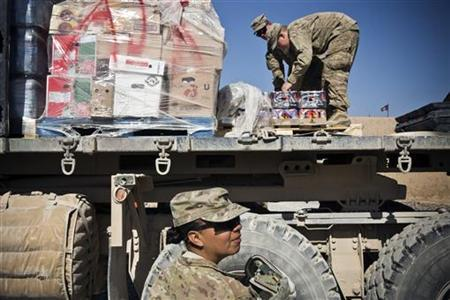 Specialist Joanne Read, of the U.S. Army's Bravo Company, 1st Battalion, 36th Infantry Regiment, First Armored Division, helps unload a resupply truck at Command Outpost AJK (short for Azim-Jan-Kariz - a near-by village) in Maiwand District, Kandahar Province January 24, 2013. REUTERS/Andrew Burton