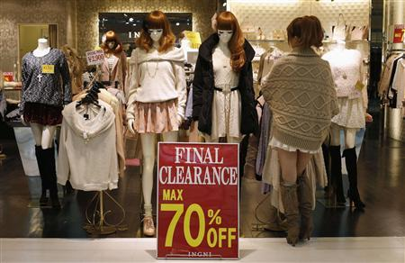 A woman works next to a sale sign at a shopping district in Tokyo January 24, 2013. REUTERS/Toru Hanai