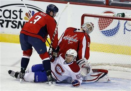 Washington Capitals goalie Michal Neuvirth reacts after David Desharnais (51) of the Montreal Canadiens crashed the crease during their NHL hockey game in Washington January 24, 2013. REUTERS/Kevin Lamarque