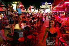 Туристы смотрят представление в исполнении транссексуалов в баре в Патонге на острове Пхукет 5 января 2005 года. Таец и его подруга заходят в мебельный магазин. Увидев подушку, девушка приходит в восторг, и неожиданно ее нежный женский голос опускается и превращается в мужской. Шокированный мужчина в испуге убегает от своей возлюбленной. REUTERS/Kin Cheung