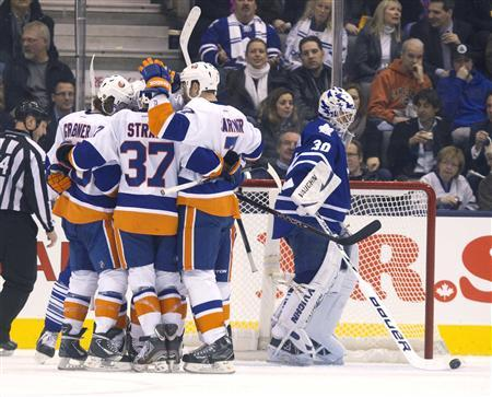 The New York Islanders celebrate next to Toronto Maple Leafs' goalie Ben Scrivens after Islanders Brad Boyes scored in the second period of their NHL hockey game in Toronto January 24, 2013. REUTERS/Fred Thornhill