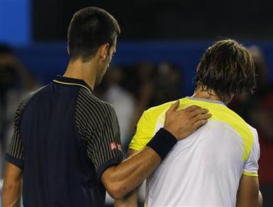 Novak Djokovic of Serbia (L) places his hand on the back of David Ferrer of Spain after defeating him in their men's singles semi-final match at the Australian Open tennis tournament in Melbourne, January 24, 2013. REUTERS/Damir Sagolj
