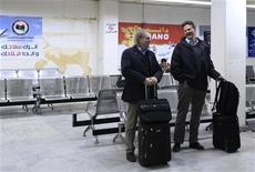 Responsables de Estados Unidos y Europa están minimizando el riesgo para los estadounidenses por las últimas amenazas de milicianos islamistas, que han prometido atacar a occidentales en la ciudad libia de Bengasi. En la imagen, dos pasajeros esperan para subir a un avión en el aeropuerto de Bengasi tras las recomendaciones de las autoridades europeas a sus ciudadanos, el 24 de enero de 2013. REUTERS/Esam Al-Fetori