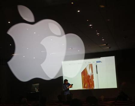 Apple's logo is reflected on a glass panel while a staff of the Apple store explains about the iPad at a seminar at its shop in Tokyo January 18, 2013. Sharp's iPad screen production line at its Kameyama plant in central Japan has fallen to the minimal level to keep the line running this month after a gradual slowdown began at the end of 2012 as Apple manages its inventory, the industry sources with knowledge of Sharp's production plans told Reuters. REUTERS/Kim Kyung-Hoon (JAPAN - Tags: BUSINESS)