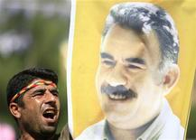 A Kurdish man displays a picture of jailed PKK leader Abdullah Ocalan as he shouts slogan during a peace day rally in the southeastern Turkish city of Diyarbakir September 1, 2009. REUTERS/Osman Orsal