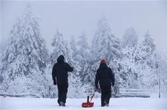 People pull a sledge as they walk through freshly fallen snow at the Feldberg mountain, 25km (15 miles) north-west of Frankfurt, December 11, 2012. REUTERS/Kai Pfaffenbach (GERMANY - Tags: ENVIRONMENT)