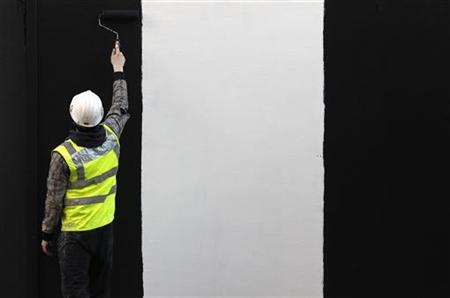 A worker paints a wall on a construction site in London January 5, 2011. REUTERS/Stefan Wermuth