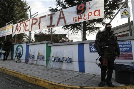 A riot policeman stands in front of a banner at a metro depot in Athens January 25, 2013. REUTERS/Yannis Kolesidis