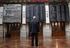 Трейдер смотрит на табло с рыночной информацией на фондовой бирже в Мадриде 12 июня 2012 года. Европейские акции растут после публикации отчета о деловом климате Германии. REUTERS/Andrea Comas