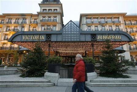 People walk past the luxurious Victoria Jungfrau hotel at the Swiss mountain resort of Interlaken in this December 15, 2009 file photo. REUTERS/Arnd Wiegmann
