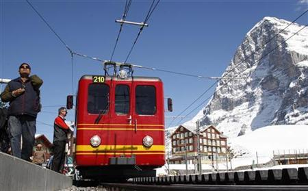 Tourists walk past a train of the Jungfrau Railways at the Kleine Scheidegg station (altitude 2061 metres/6762 feet) near the Swiss mountain resort of Grindelwald, April 26, 2012. REUTERS/Christian Hartmann/Files